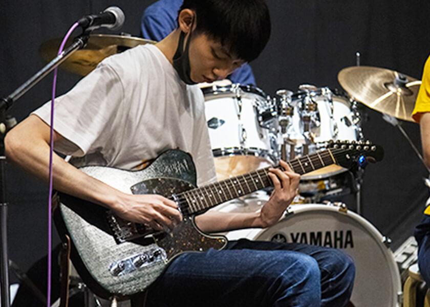自慢のギターを演奏する渋谷さん